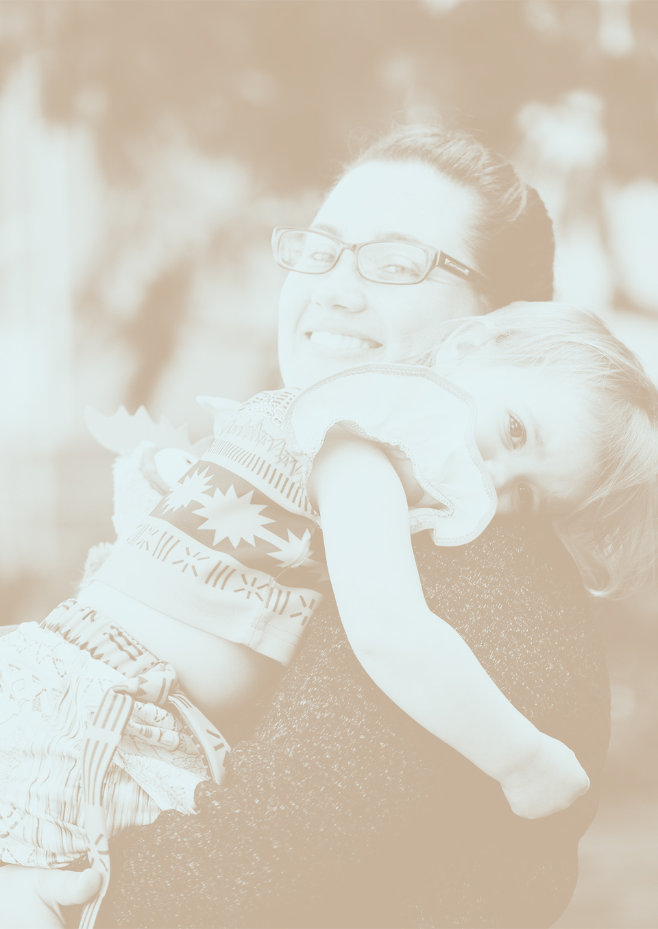 A smiling woman holding a child.