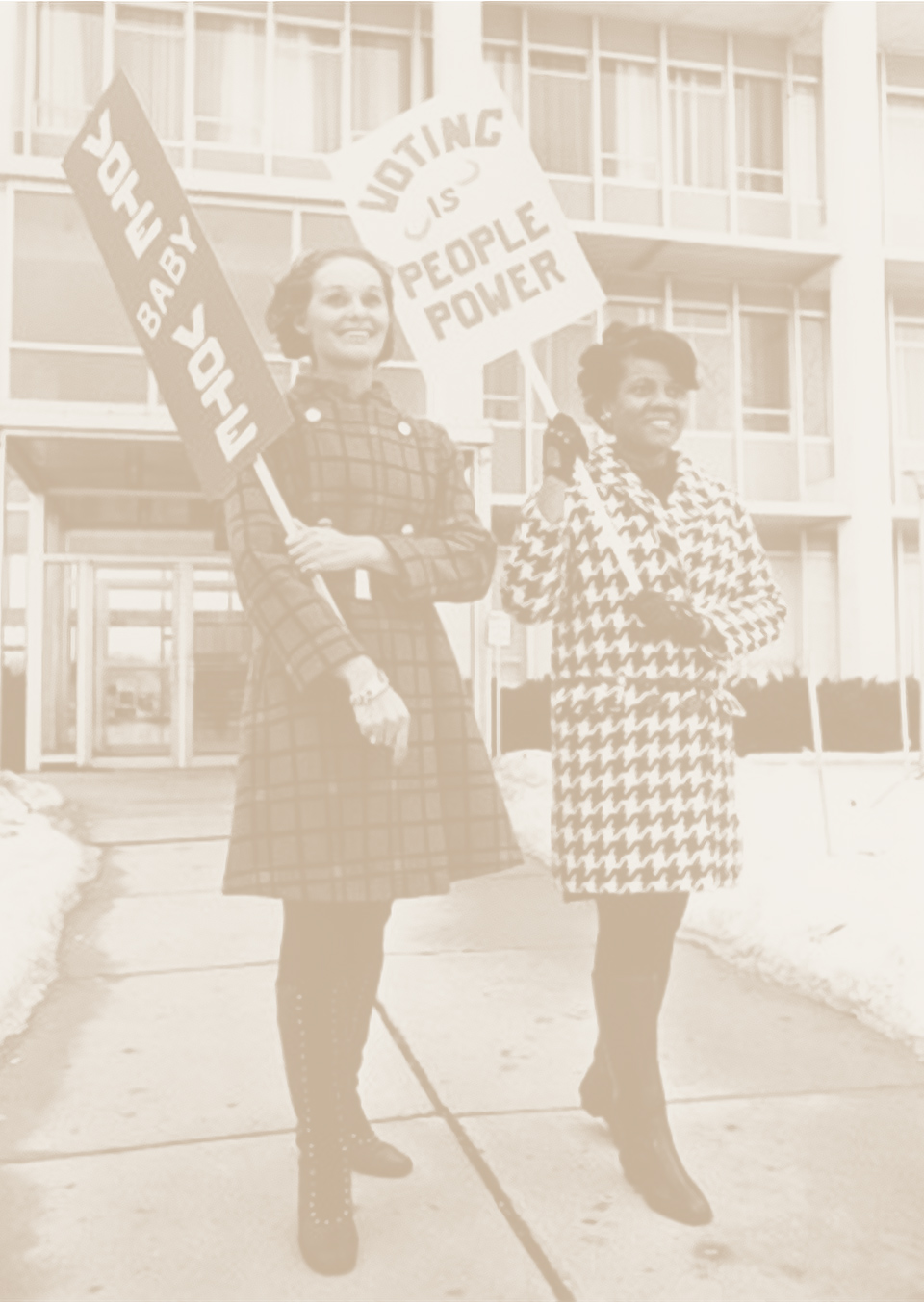 Two women encouraging voting with picket signs.