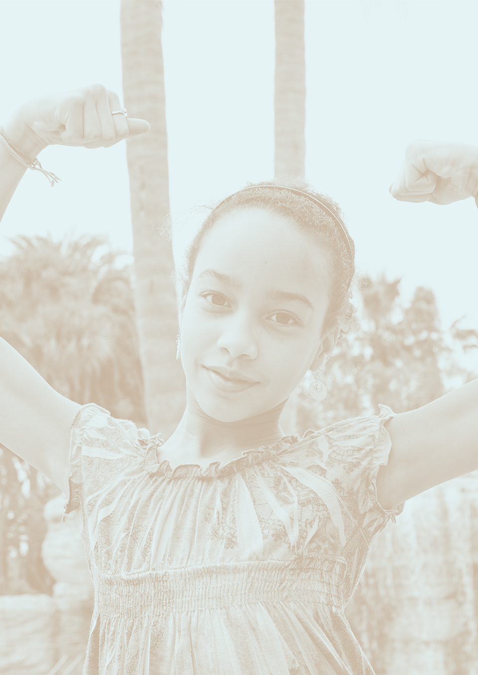 Young woman with arms up, flexing to demonstrate her strength.