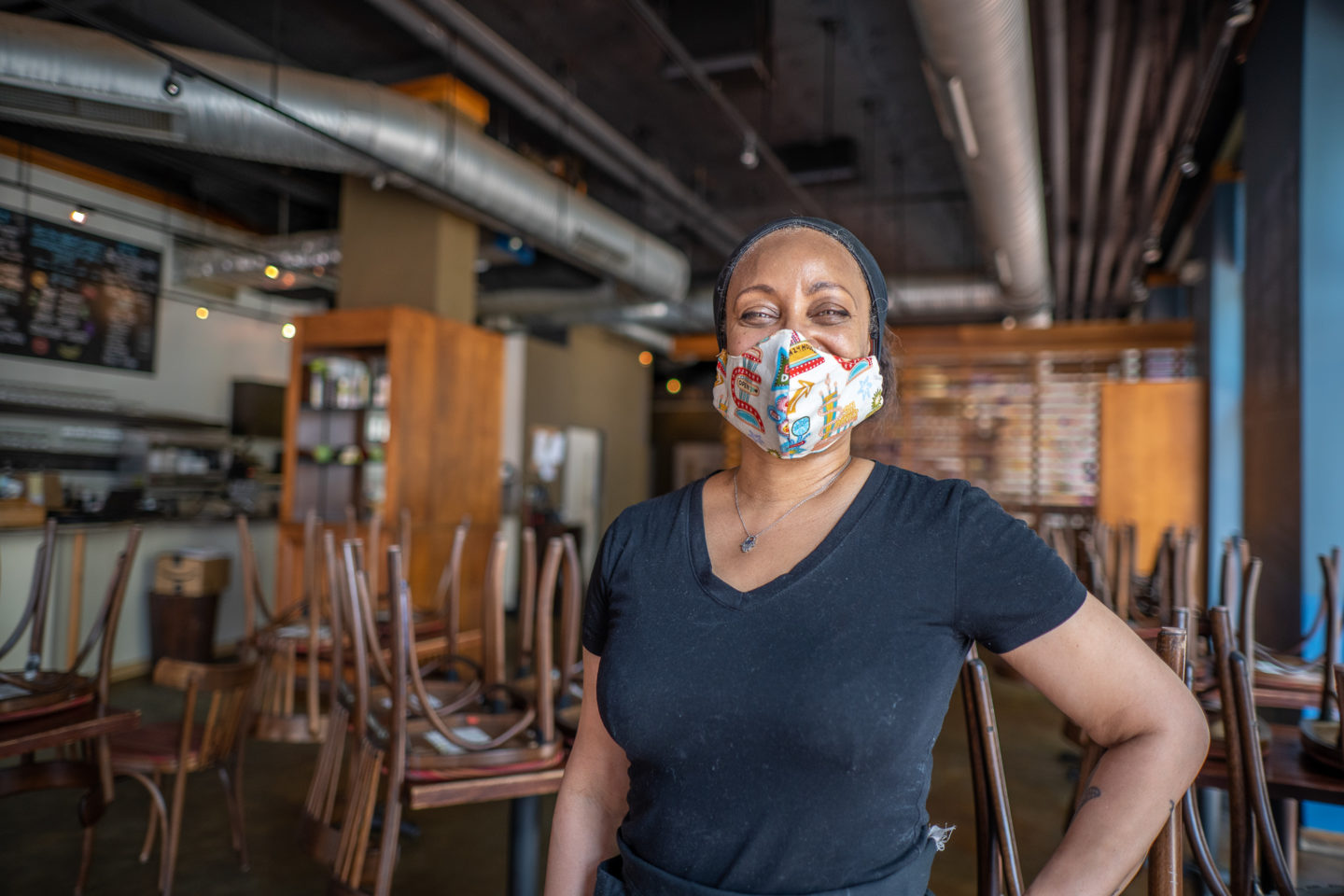 Image of woman wearing mask, working in a restaurant.