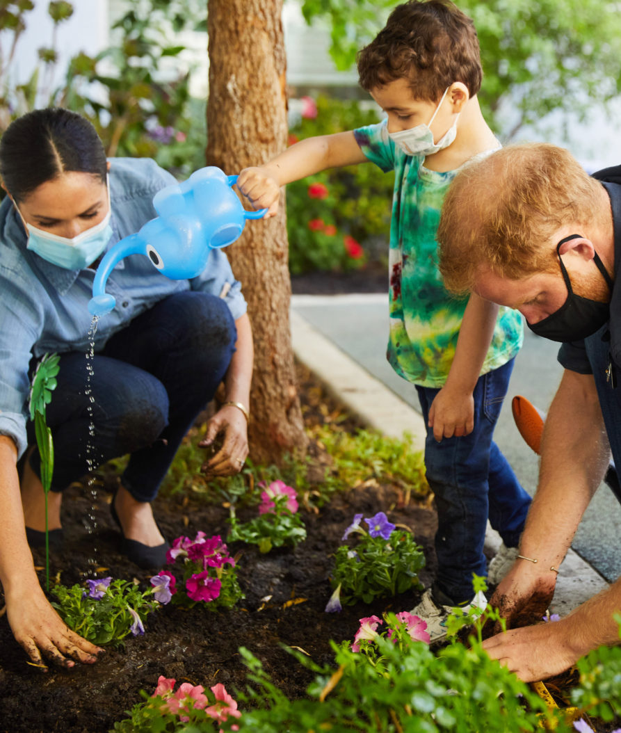 Meghan and Harry, pictured next to a child watering plants, helping replant a preschool's garden in LA.