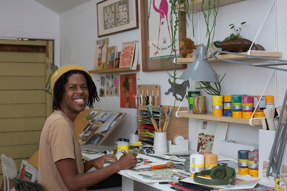 Christian Robinson, the author of The Bench smiles at his work station