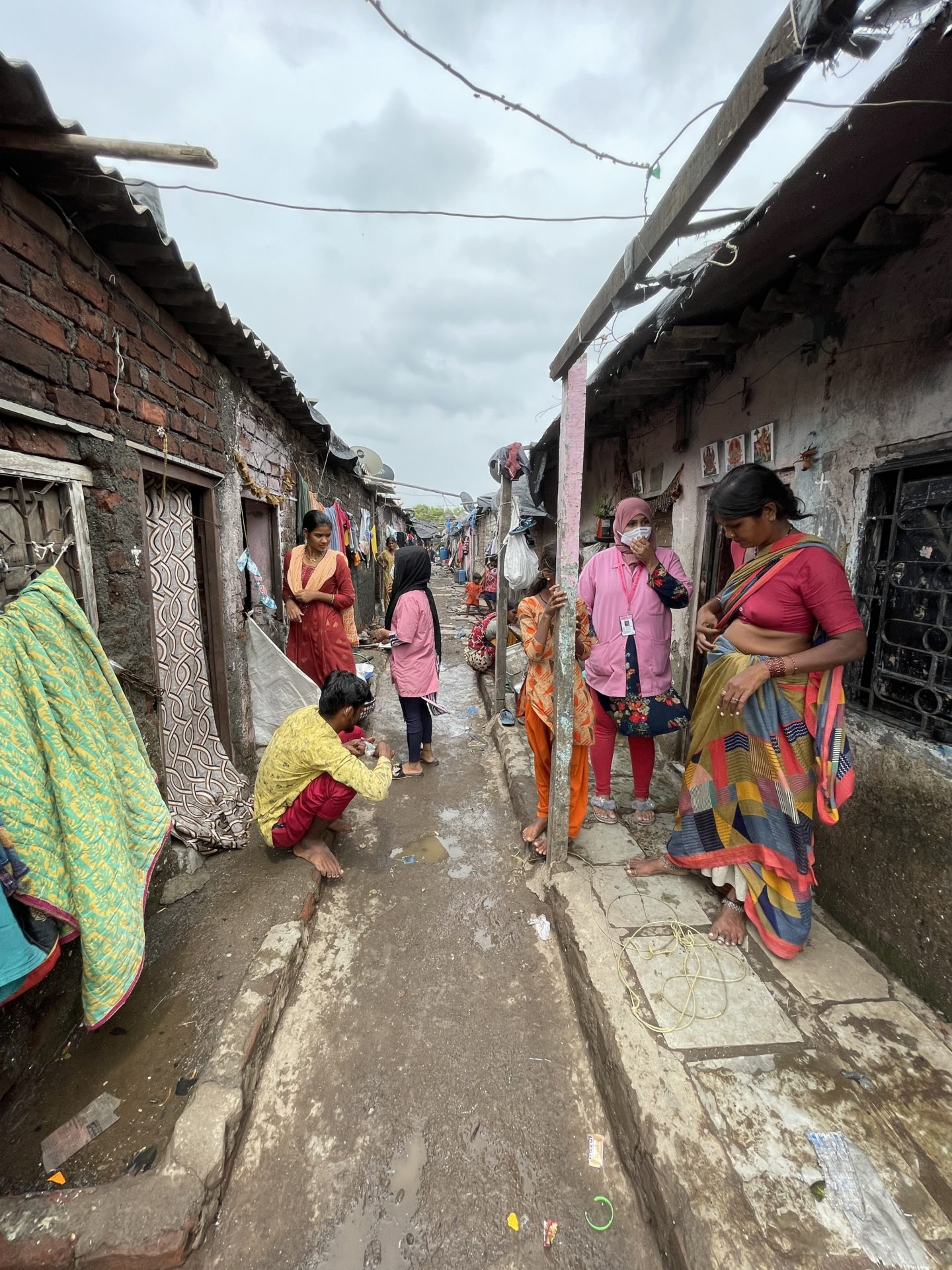 In this photo, it is a cloudy day when Uzma and Mariam from Myna Mahila Foundation are at the doorstep of some destitute families living in a Mumbai transit camp. They stand in a narrow alleyway with slums on both sides, clothes hanging to dry and electric wires in the sky. They are speaking to the slum residents about their health and livelihood situation and asking them to go to Myna's mobile clinic for support.