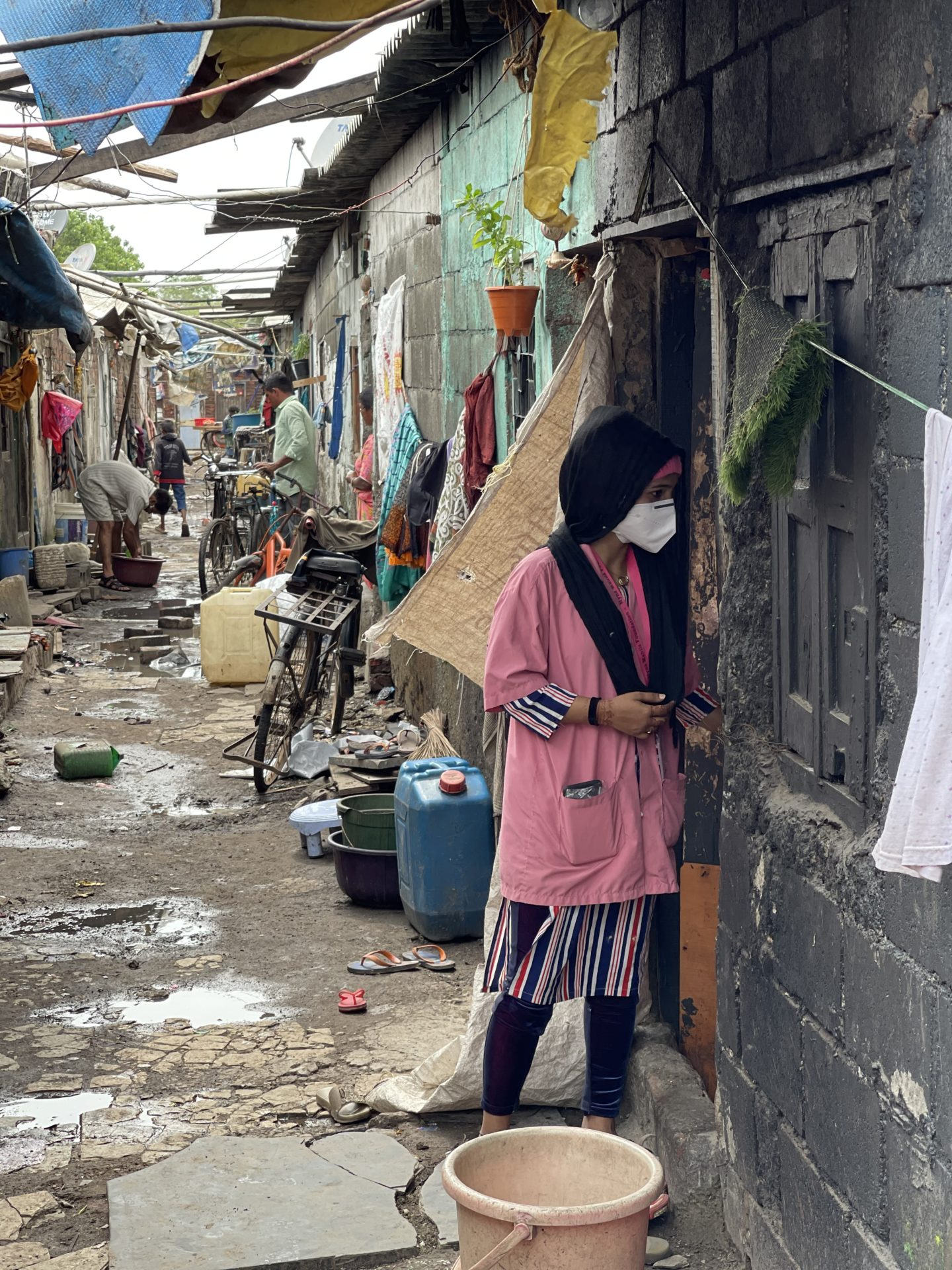 In this photo, Mariam from Myna Mahila is wearing a facemask and speaking at the doorstep of someone in a shack in a slum. The houses all have aluminium roofs, lots of sticks, and water containers on the floor to store water. She is in a narrow alleyway with slums on both sides.