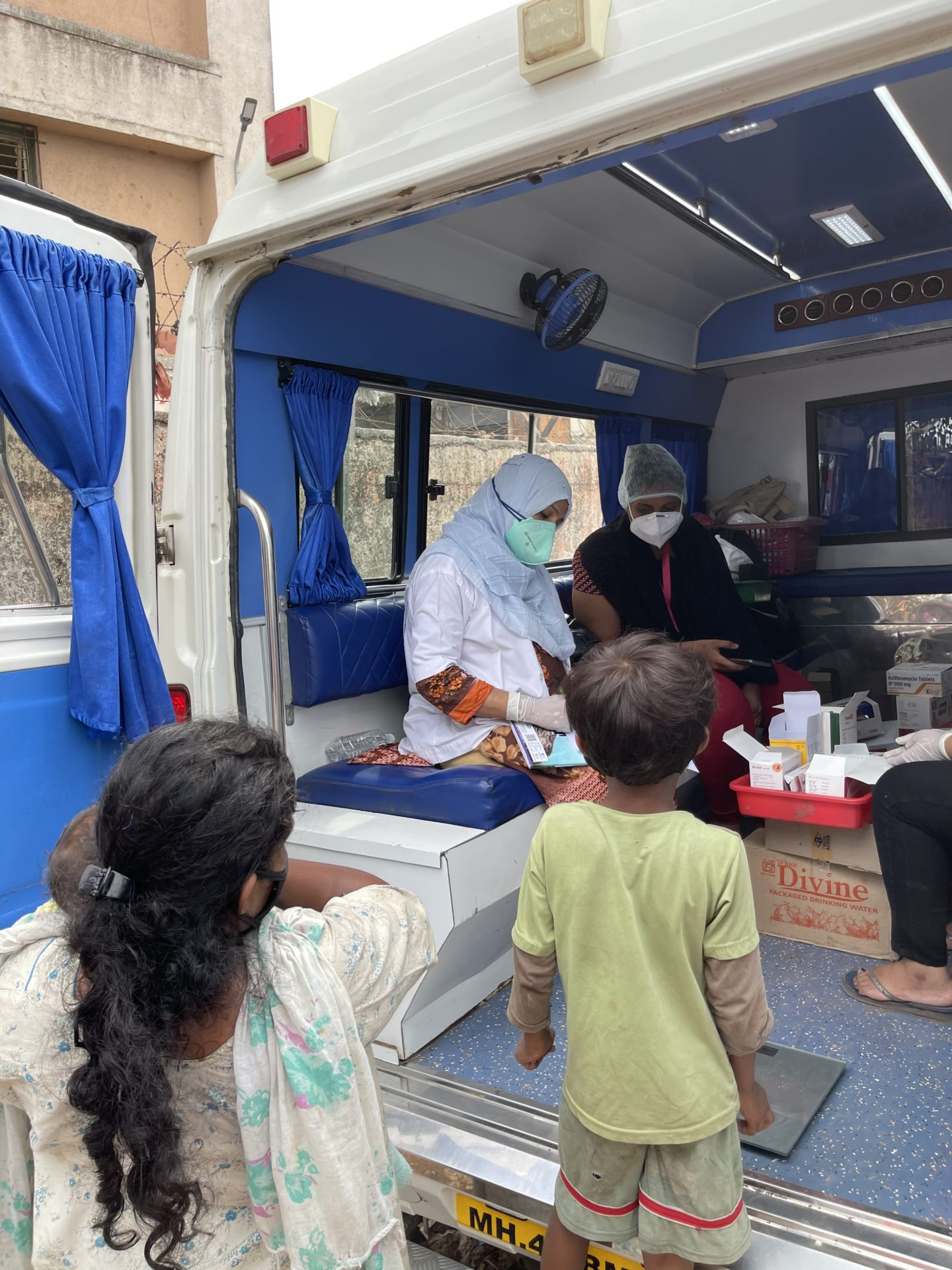 In this photo, one of Myna's doctors and nurses is sitting inside the mobile clinic checking on some patient case forms while a young woman peers on. She is holding a baby in her arms and her young son stands at the edge of the vehicle looking at the doctor at work.