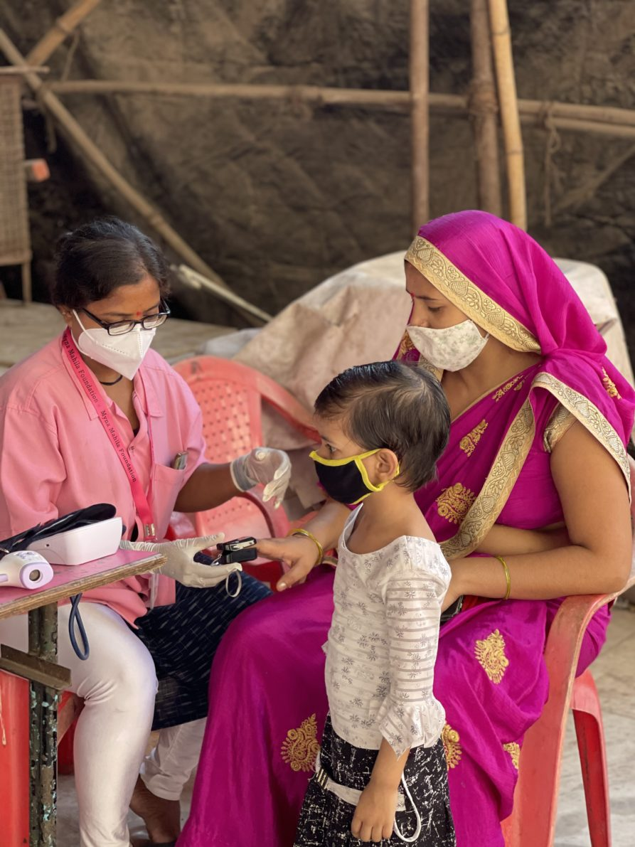 In this photo, Sapna from Myna Mahila is checking a woman's Oxygen concentration using an Oximeter on her finger. The patient is wearing a bright pink sari and Sapna wears a pink lab coat. The patient's young daughter stands and stares at the health devices on the table in front of Myna's mobile clinic.